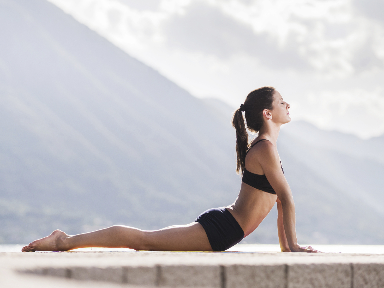 Side view of a young woman in cobra pose.